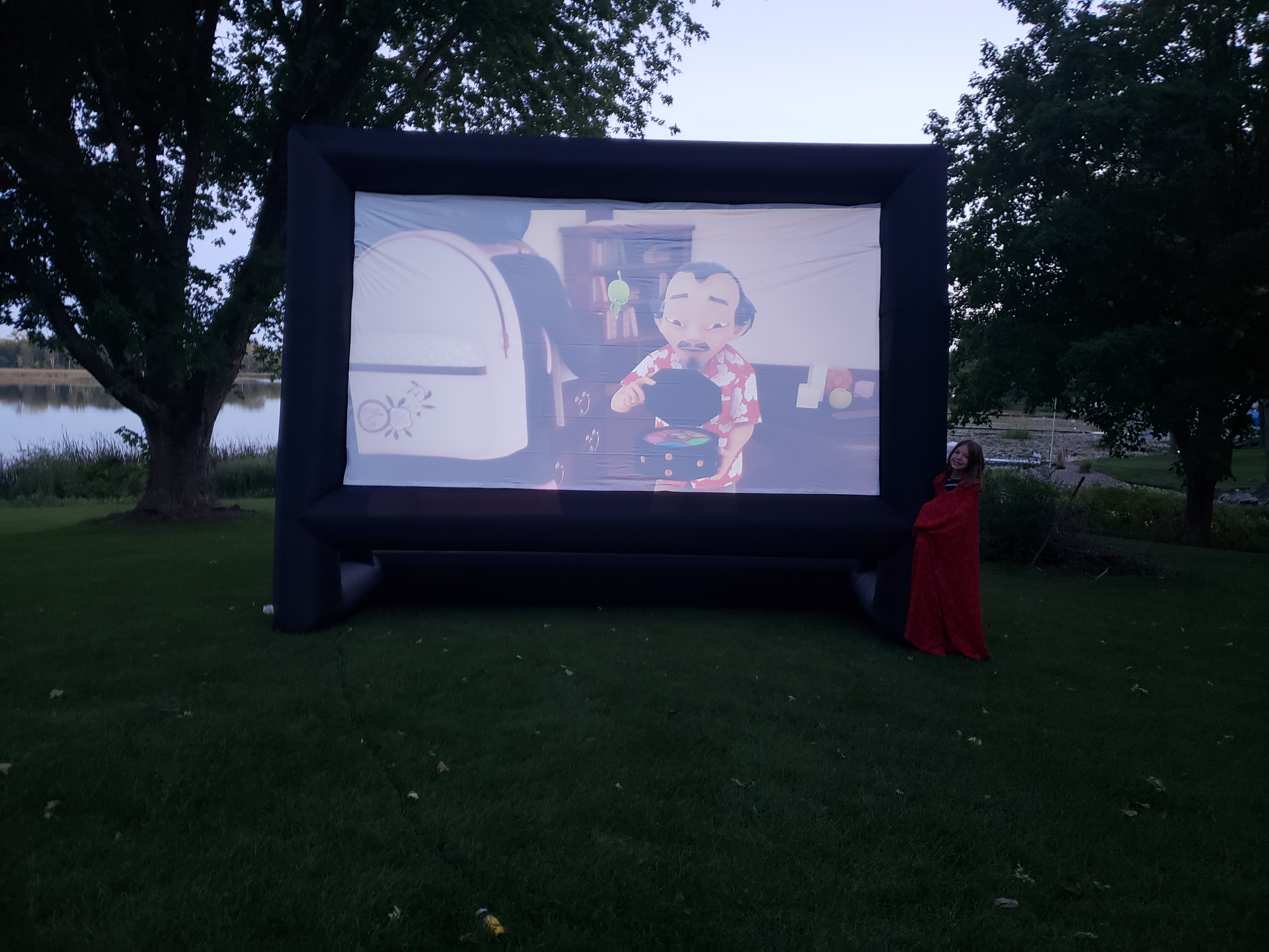 Our daughter Lily standing by the blow-up screen during our test-run at the lake this past Sunday.